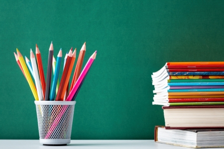 hard bound: Stack of colorful textbooks and copybooks with pencils near by on background of blackboard