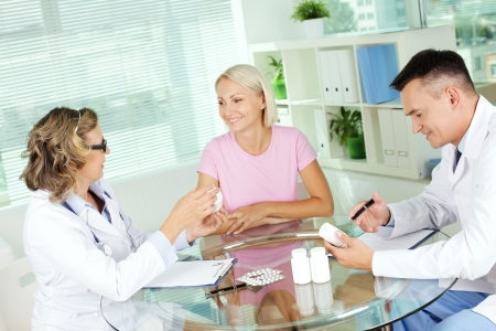 Portrait of confident practitioners describing new vitamins to patient in hospital photo