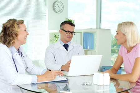 doctor computer: Doctors interacting with patient at medical consultation