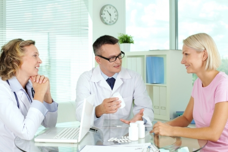 Doctor describing vitamins to patient at medical consultation Stock Photo