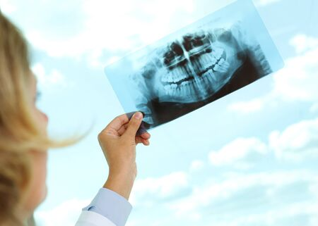 Image of female doctor holding and looking at x-ray photo