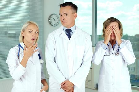 white coats: Three clinicians in white coats in shock Stock Photo