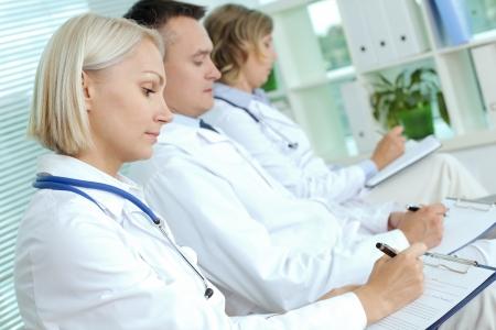 personal medico: Retrato de tres m�dicos con portapapeles haciendo notas en una conferencia m�dica
