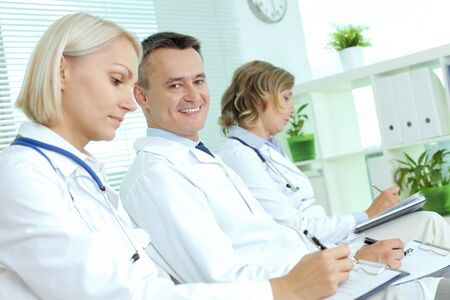 clinician: Portrait of happy male clinician making notes at medical conference between his colleagues Stock Photo