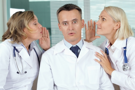 Portrait of surprised male clinician between two gossiping women photo