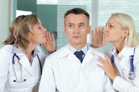 clinician: Portrait of pensive male clinician between two gossiping women