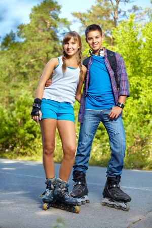 rollerskating: Couple of happy teens on roller skates looking at camera outside