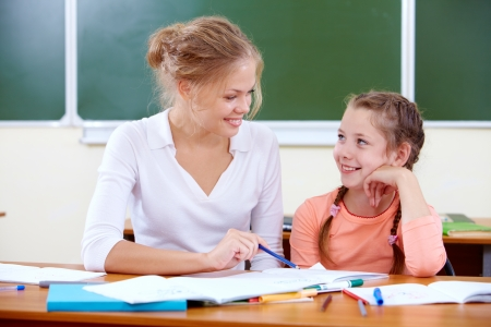 teaching children: Portrait of lovely girl and her teacher drawing at lesson