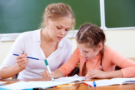small group of people: Portrait of lovely girl and her teacher drawing at lesson