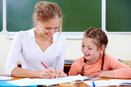 kids painting: Portrait of young teacher showing her pupil how to draw at lesson