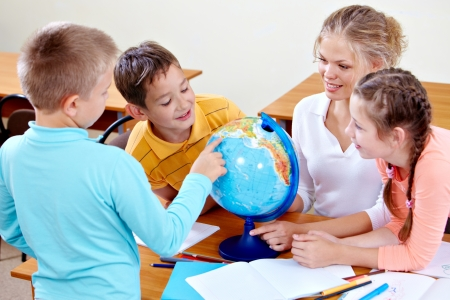 child learning: Portrait of cute schoolchildren and teacher looking at globe at geography lesson