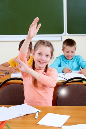 Portrait of lovely girl raising hand at workplace with schoolboys on background photo