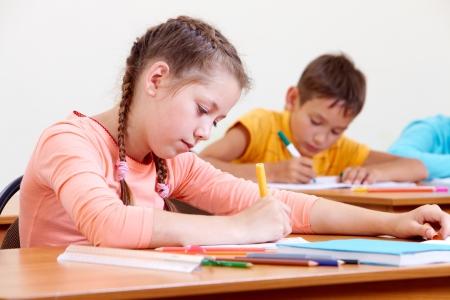 ni�os dibujando: Retrato de dibujo muchacha encantadora en cuaderno escolar con el fondo Foto de archivo