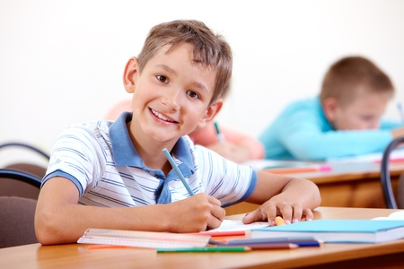 lad: Portrait of smart lad looking at camera with classmates on background Stock Photo
