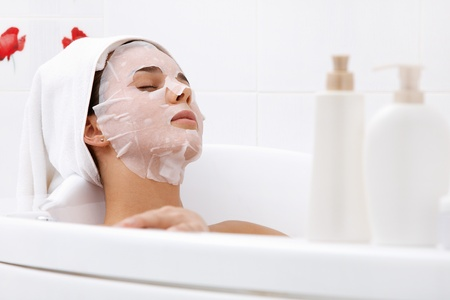 Image of serene woman with facial mask enjoying bath in spa salon photo