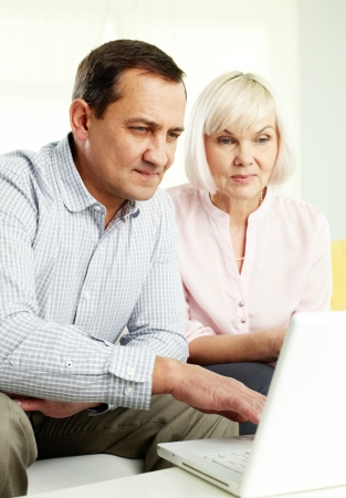 Portrait of mature man and his wife working with laptop at home Stock Photo - 14991449
