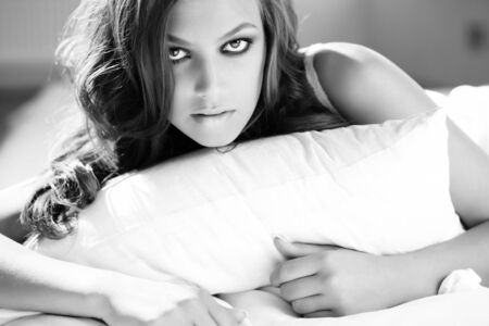 maquillage: Posh young woman lying in bed and looking at camera