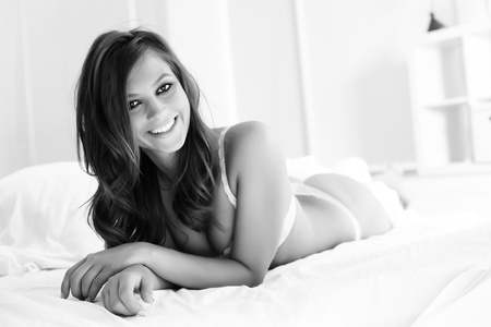 lying in bed: Happy young woman in lingerie lying in bed and looking at camera  Stock Photo