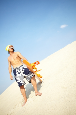 Portrait of a handsome guy holding a snowboarder on the beach Stock Photo - 14991365