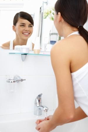 spiegelbeeld: Afbeelding van mooie vrouwelijke kijken in spiegel terwijl het wassen van haar handen in de ochtend