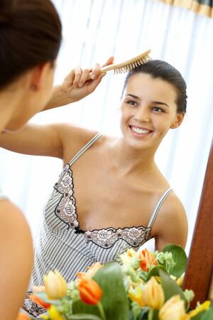 Image of pretty female with hair brush looking in mirror with smile photo