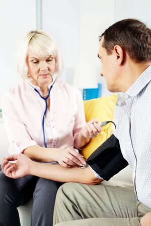 stephoscope: Portrait of mature woman measuring blood pressure of her husband at home Stock Photo