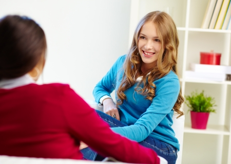 amigas conversando: Retrato de ni�a feliz mirando a su amigo con una sonrisa durante la conversaci�n