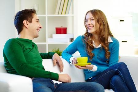 mujeres sentadas: Retrato de los amigos alegres mirando el uno al otro durante la conversación