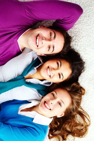 Above angle of three laughing friends lying on the floor and looking at camera Stock Photo - 15104292