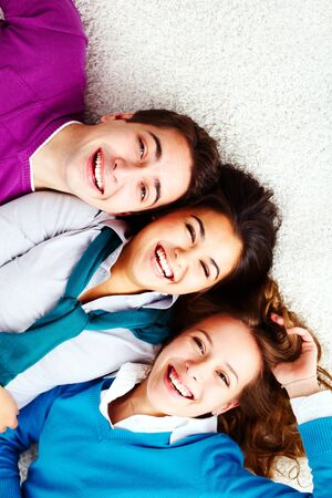 Above angle of three laughing friends looking at camera Stock Photo - 15104287