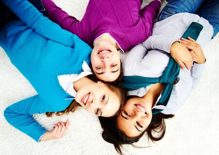 Above angle of attractive friends looking at camera while lying on the floor Stock Photo - 15104281