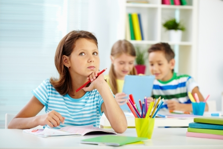Portrait of lovely girl concentrating on drawing at workplace with schoolmates on background Imagens