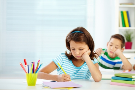 schoolmate: Portrait of serious girl drawing at workplace with her schoolmate on background