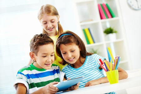 elementary students: Portrait of happy classmates at workplace using digital tablet