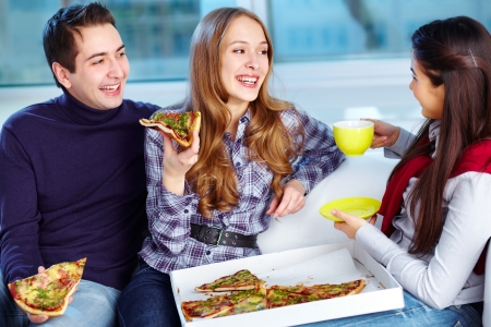 eating pizza: Image of happy teenage friends eating pizza together Stock Photo