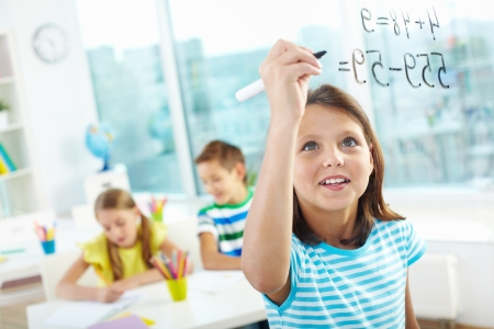 sums: Portrait of lovely girl doing sums on transparent board with two schoolmates on background