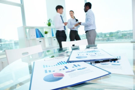 Image of business documents with working team communicating at background Stock Photo - 15095975