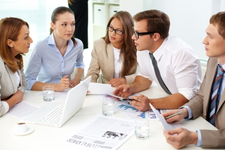 collaboration: Image of confident partners looking at their colleague at meeting Stock Photo