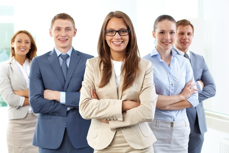 competitive business: Portrait of five businesspeople looking at camera with female leader in front