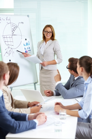 explain: Confident businesswoman explaining something to colleagues at meeting