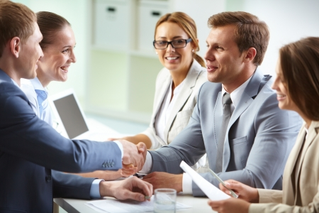 consulting team: Image of confident businessmen handshaking at meeting