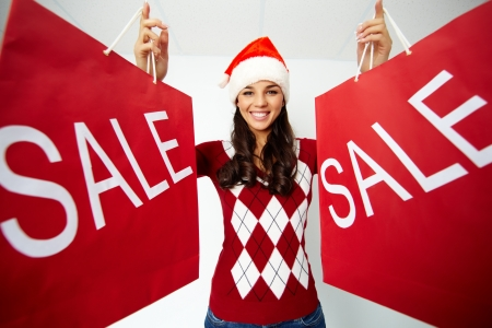 paperbags: Happy girl in Santa cap holds red paperbags with symbol of sale Stock Photo