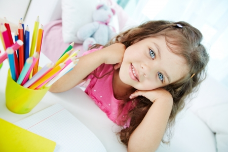 Portrait of lovely girl looking at camera with colorful pencils near by