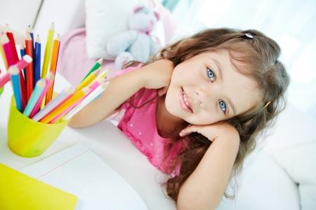niños en la escuela: Retrato de muchacha hermosa que mira la cámara con lápices de colores por cerca de Foto de archivo