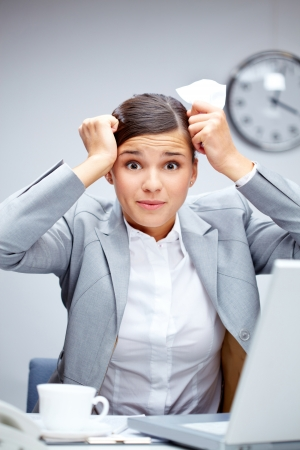 oops: Image of young employer touching her head in confusion at workplace