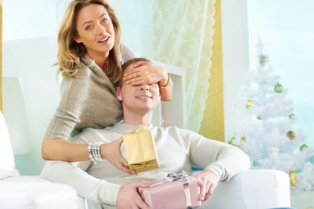 Happy woman making surprise to her husband on Christmas day photo