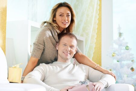 Happy woman and her husband having rest at home on Christmas day photo