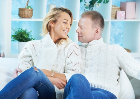 pullovers: Happy couple in white pullovers and jeans looking at one another while sitting at home Stock Photo