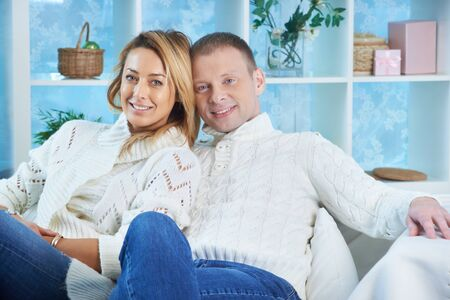 pullovers: Happy couple in white pullovers and jeans looking at camera at home