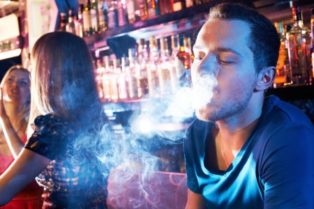 letting: Portrait of young man letting smoke out of mouth while smoking hookah Stock Photo